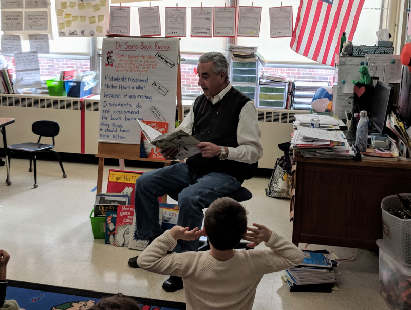 Rotarian John Monteleone reads to students